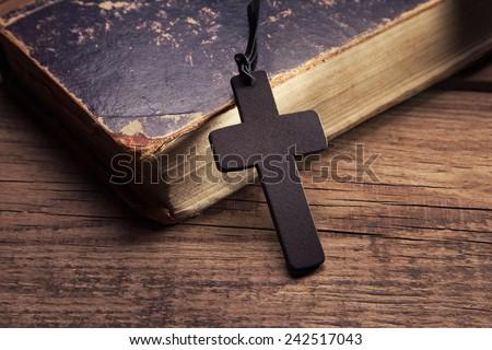 Closeup of wooden Christian cross on bible - stock photo