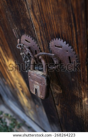 Closeup of wooden door, locked with old-fashioned Padlock - stock photo