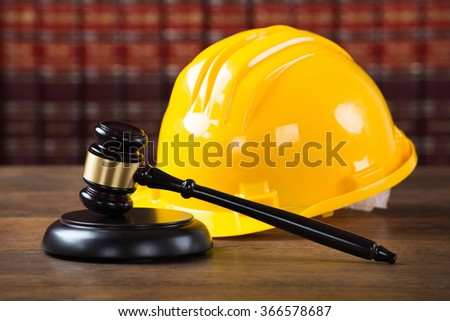 Closeup of wooden mallet and yellow hardhat on table in courtroom - stock photo