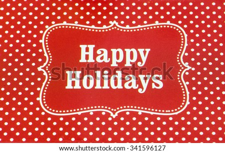 "Closeup of written Red and white ""Happy Holidays"" greeting on red and white polka dot background. - stock photo"