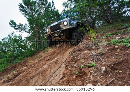 Closeup of 4x4 truck driving downhill on the edge - stock photo