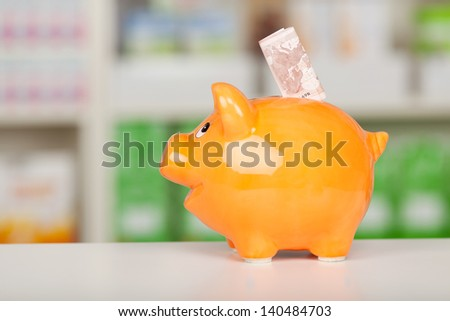 Closeup of yellow piggybank with euro note on pharmacy counter - stock photo