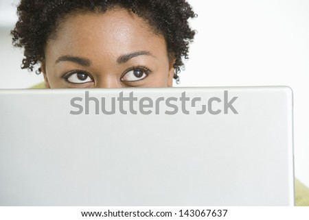 Closeup of young African American woman with laptop looking up - stock photo