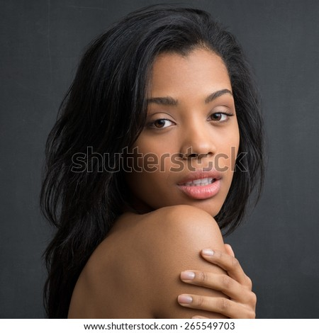 Closeup of young african woman looking at camera over her shoulder  - stock photo