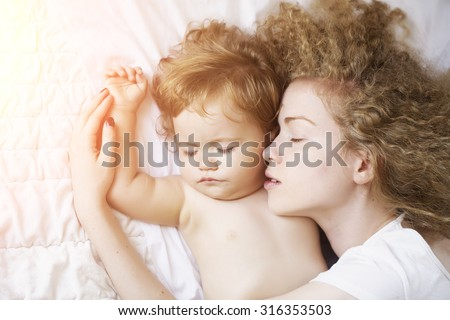 Closeup of young attractive loving mother with light blonde curly hair touching small tiny cute male lovely baby sleeping indoor in bed with white linen lying close to each other, horizontal picture - stock photo