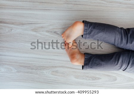 Closeup of young barefoot child laying down on the floor - stock photo