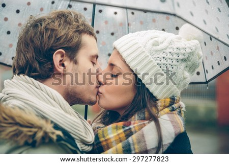 Closeup of young beautiful couple kissing under the umbrella in an autumn rainy day. Image focused on the lips. - stock photo
