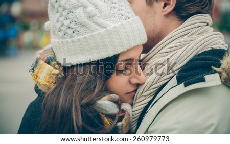 Closeup of young beautiful couple with hat and scarf embracing in a cold autumn day. Love and couple relationships concept. - stock photo