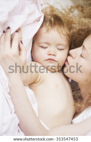 Closeup of young beautiful loving mother with light blonde curly hair kissing little tiny cute male lovely baby sleeping indoor in bed with white linen lying close to each other, vertical picture - stock photo