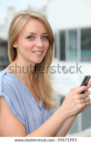 Closeup of young blond woman with mobile phone - stock photo