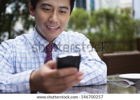 Closeup of young businessman using cell phone at outdoor cafe - stock photo