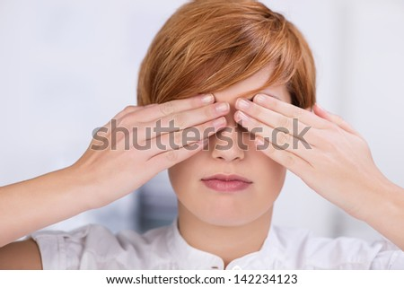 Closeup of young businesswoman covering eyes with hands in office - stock photo