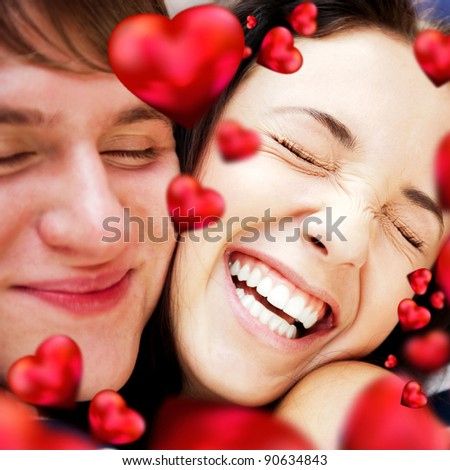 Closeup of young couple embracing and very happy to be together. Valentine concept. Red hearts are flying around them - stock photo