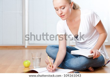 Closeup of young female student sitting on the floor and taking notes, studying and organizing with healthy snack including apple and fresh water - stock photo