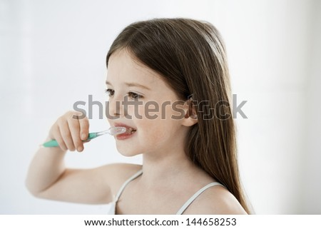 Closeup of young girl brushing teeth - stock photo