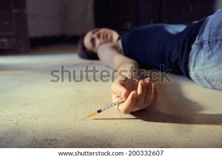 Closeup of young girl in heroine overdose holding syringe and lying on pavement. Copy space - stock photo