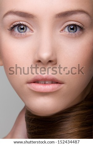 Closeup of young girl with natural, beautiful lips and eyes. Studio shot on neutral background. - stock photo