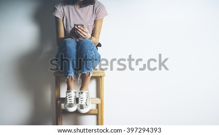 Closeup of young hipster girl wearing ripped jeans and using smart phone while sitting on a chair, blank white background with copy space for your content or design - stock photo