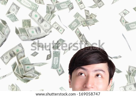 closeup of young man looking up money falling, isolated on white background, asian man - stock photo