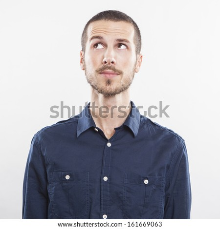 Closeup of young man looking up thinking on white background - stock photo