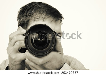 Closeup of young man with professional camera isolated on white background - stock photo