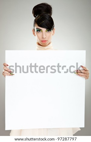 Closeup of young, pretty fashion woman in dress standing near huge blank board and holding it. Lots of copyspace for your text and logo - stock photo