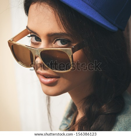 Closeup of Young sexy woman in blue cap and jeans jacket  looking through golden sunglasses .  Outdoors, lifestyle. - stock photo