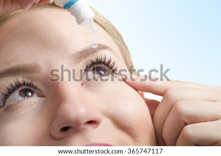 Closeup of young woman applying eye drops, selective focus only on right eye. Drop captured in mid air/ eye drops with vitamins/ eye care - stock photo