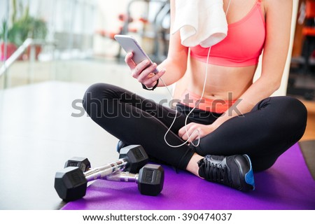 Closeup of young woman athlete sitting on mat and using mobile phone in gym - stock photo