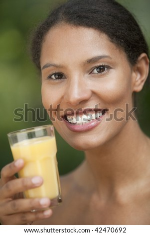 Closeup of young woman drinking orange juice in outdoor setting. Vertically framed shot. - stock photo