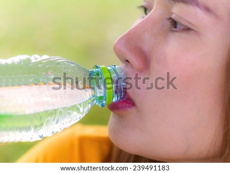 Closeup of young woman drinking water at workout outdoors. - stock photo