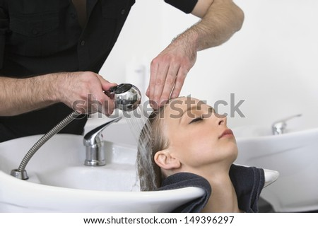 Closeup of young woman getting hair wash from hairdresser in salon - stock photo