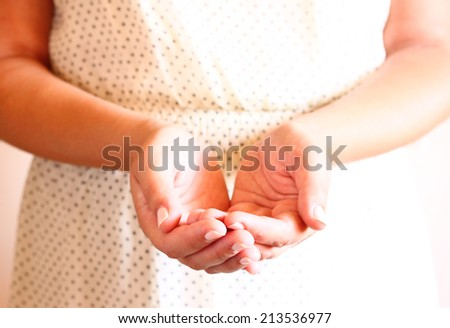 closeup of young woman hands, outstreched in cupped shape. selective focus. natural light. - stock photo