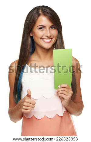 Closeup of young woman holding a green banner ad and gesturing thumb up, over white background - stock photo
