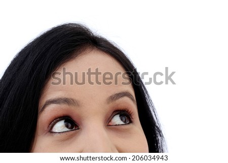 Closeup of young woman looking up against white background - stock photo