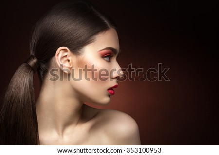 Closeup of young woman profile with red lips. Over dark background. Copy space. - stock photo
