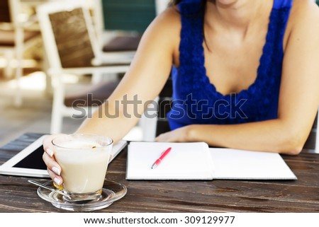 Closeup of  young woman relaxing with coffee while sitting at a table in a  sidewalk cafe.  - stock photo