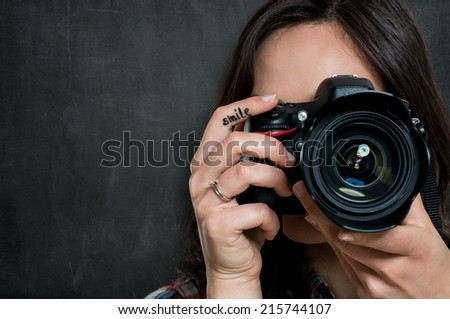 Closeup Of Young Woman Using Camera Over Gray Background - stock photo
