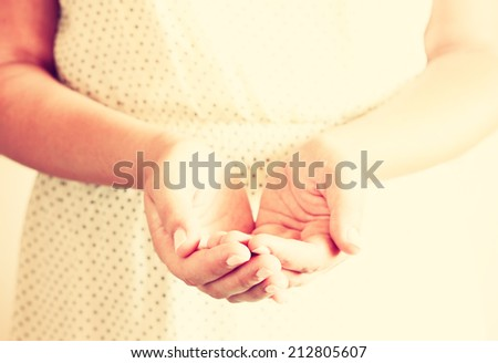 closeup of young woman with outstretched hands in cupped shape. selective focus. retro toned image. - stock photo
