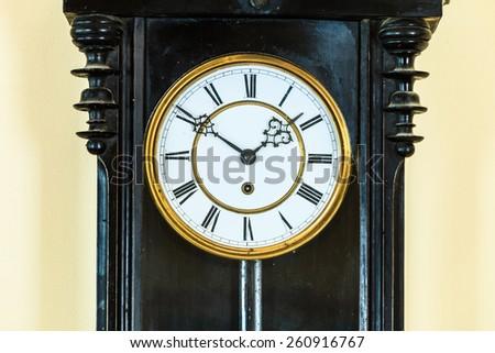 Closeup old big wooden pendulum clock hanging on wall - stock photo