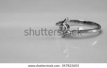 Closeup old diamond ring on blurred marble floor background in black and white tone - stock photo