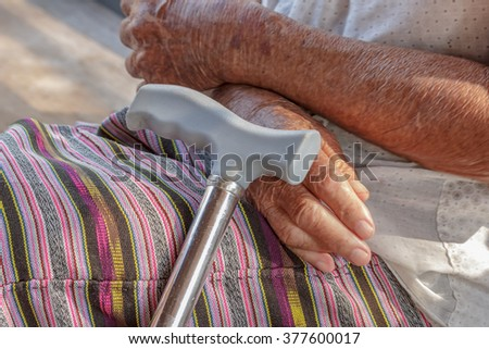 Closeup old hand with crutch (hand movement) - stock photo