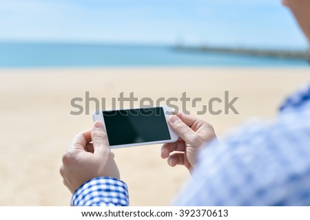 Closeup on a man holding phone on the beach, outside background, sunny day - stock photo