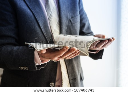 Closeup on a man reading a magazine. Tinted.  - stock photo