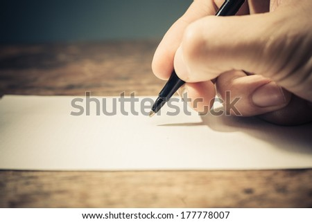 Closeup on a man's hand writing on apiece of paper with a pen - stock photo