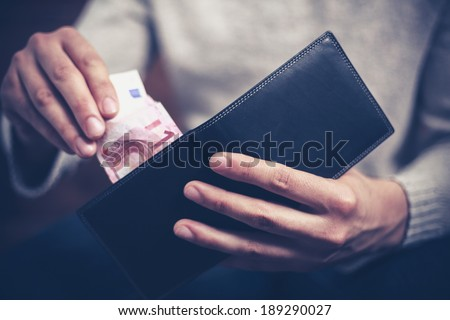 Closeup on a man's hands as he is getting a banknote out of his wallet - stock photo