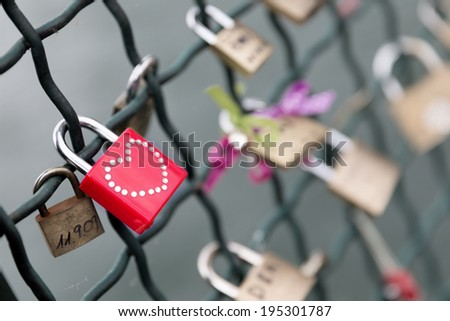 Closeup on a red padlock with a studded heart on a bridge railing. Selective focus on the red padlock. - stock photo