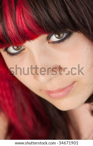 Closeup on a serious young woman with partially dyed red brunette hair and large brown eyes. - stock photo
