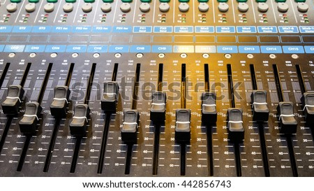Closeup on a sliders of a mixing console. It is used for audio signals modifications to achieve the desired output. Applied in recording studios, broadcasting, television and film post-production. - stock photo