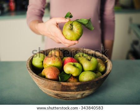 Closeup on a young woman's hand as she is standing in her kitchen and is holding an apple from a bowl of apples - stock photo